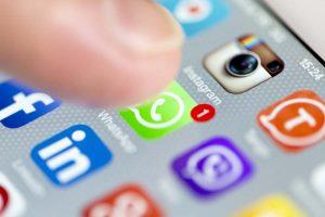 dedo clicando no WhatsApp Business na tela do celular