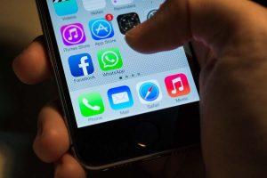 pessoa segurando o celular com facebook e WhatsApp Business na tela