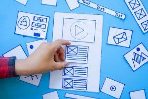 Mão tocando um desenho que imita a programação de um site para exemplificar a experiência do usuário